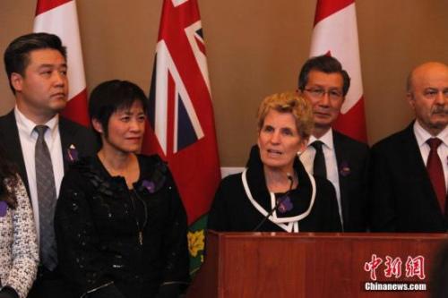 """在南京大屠杀80周年之际,当地时间2017年12月13日,加拿大安大略省省议会举行南京大屠杀纪念活动。图为安省省长韦恩(中)受邀出席纪念会,表示支持华人社区开展南京大屠杀纪念活动。这是该省省议会通过华人省议员黄素梅(左二)提出的""""将每年12月13日设立为南京大屠杀纪念日""""动议后,该省官方场合首次正式举行南京大屠杀纪念活动。<a target='_blank' href='http://www.chinanews.com/'>中新社</a>记者 余瑞冬 摄"""