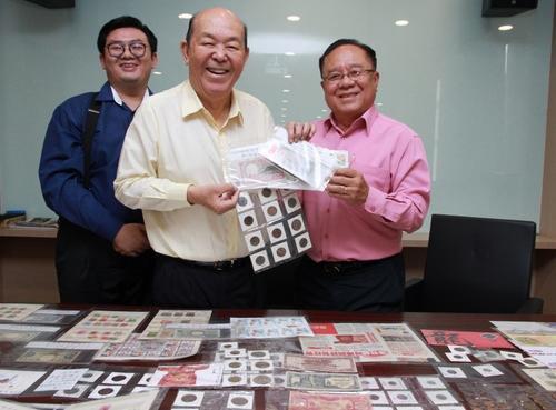 符树波(右)将珍藏的珍贵钱币和邮票,赠捐予华总马来西亚华人博物馆,由吴德芳接领。左为博物馆执行秘书林家豪。(马来西亚《星洲日报》)