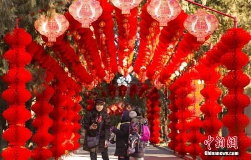 资料图:2018年2月2日,北京地坛公园,市民经过挂满红灯笼的通道。随着农历春节的临近,北京城年味渐浓。<a target='_blank' href='http://www.chinanews.com/'>中新社</a>记者 侯宇 摄
