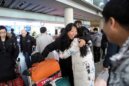 2月3日,杨玲刚下飞机后与接机的亲人相拥在一起。(欧洲时报特约记者李国庆摄)