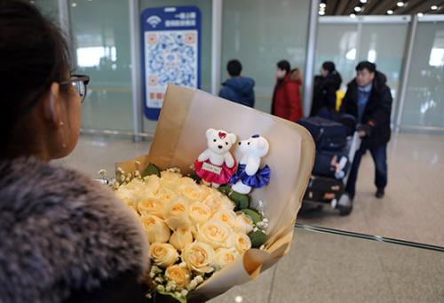一位女士携带鲜花在机场内等待亲人回中国。(欧洲时报 李国庆/摄)