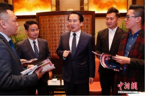 资料图:国侨办副主任谭天星(中)与海外侨胞亲切交流
