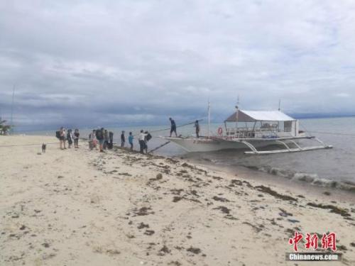"""受热带""""厄多哈""""影响,菲律宾中部宿务省马拉帕斯卡(Malapascua)岛上13日起即风雨交加,出岛交通已关闭数日,16日起停电,17日起停水。12月17日晨,风雨间隙,几艘私家船载了几十位客人出岛回宿务省达安班塔延。<a target='_blank' href='http://www.chinanews.com/'>中新社</a>记者 马天南 摄"""