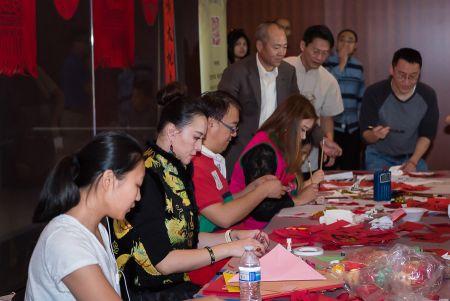 """华星艺术团的老师黄鑫带领学生现场教外国人学写""""福""""字。"""