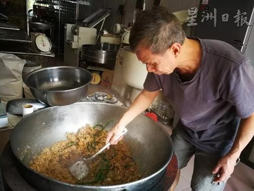 王振隆以大锅翻炒香喷喷的椰丝佐料。(马来西亚《星洲日报》记者/李慧婷 摄)