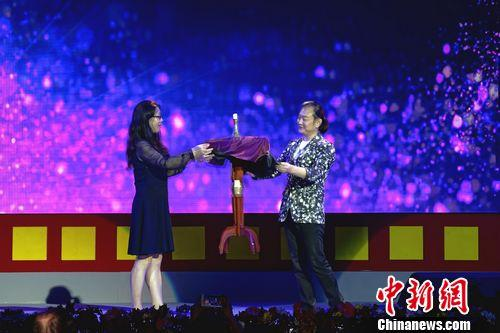 """图为中国杂技团有""""亚洲第一魔法王子""""称号的魔术师李宁(右)邀请观众一起表演《神奇魔法》。中新社 关向东 摄"""