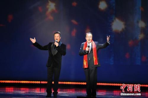 """当地时间3月6日晚,""""文化中国·四海同春""""北美艺术团文艺晚会在芝加哥市中心的卡迪拉克剧院上演。这是今年""""文化中国·四海同春""""北美团的收官演出。图为中国驻芝加哥总领事洪磊(右)登台,同著名歌唱家阎维文共同演唱经典歌曲《小白杨》。 <a target='_blank' href='http://www.chinanews.com/'>中新社</a>记者 马德林 摄"""