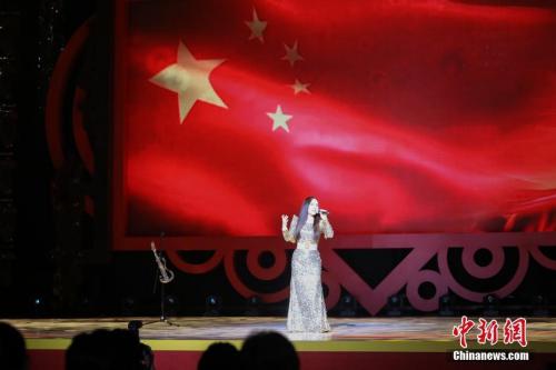 """2月4日晚,2018年""""文化中国・四海同春""""再度唱响香江。图为国家一级演员郭蓉以其独特方式演唱《红旗飘飘》。中新社记者 谢光磊 摄"""