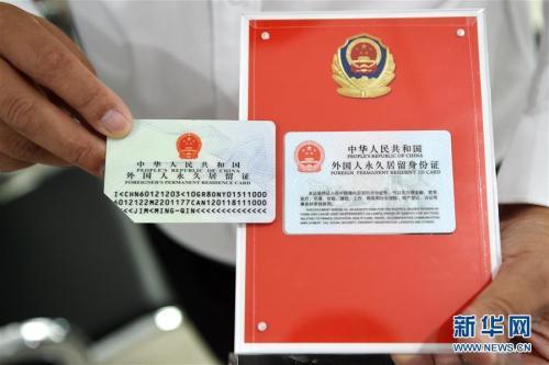 资料图:2017年6月16日,在北京市公安局出入境管理局中关村外国人服务大厅,一位外籍人士展示取得的2017版外国人永久居留身份证(右)与旧版的区别。当日,2017版外国人永久居留身份证正式启用。新华社记者 鞠焕宗 摄 图片来源:新华网