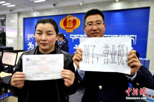 """资料图:2016年5月1日零点,拉萨市国税局西城分局顺利开出西藏首张""""营改增""""不动产经营租赁业增值税发票。该工作的推行,意味着营业税退出历史的舞台。""""营改增""""将会让企业的赋税得到不同程度的下降。 李林 摄"""