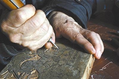 图②为任鹤林正在雕刻年画印版。