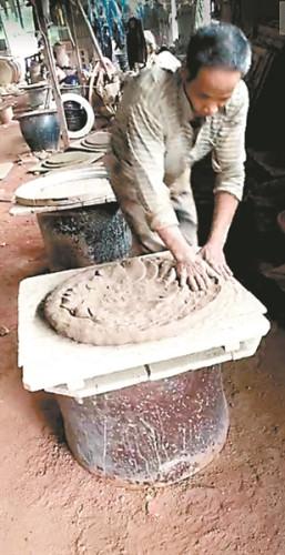 工人们仍然用古老的手工拍打瓦缸的粗胚。