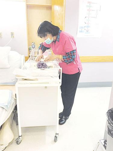 月子中心收到的查询数量大增,图为月嫂在医院照顾初生婴儿。(加拿大《明报》资料图)