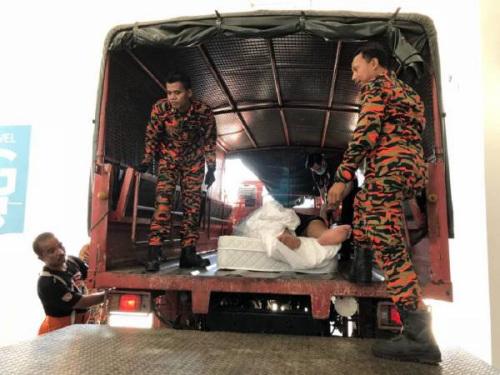 华裔男子被抬上卡车送往医院。(马来西亚《中国报》)
