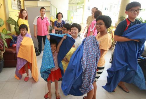 孩子们拿到百家被非常开心。(马来西亚《星洲日报》图片)