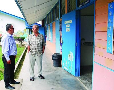 陈振淼(右)坚持让新中留在麻坑,左为陈永和校长。(马来西亚《光华日报》)