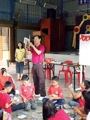 友族学生也穿上红彤彤的衣服,学习剪纸中华文化。(马来西亚《光华日报》)