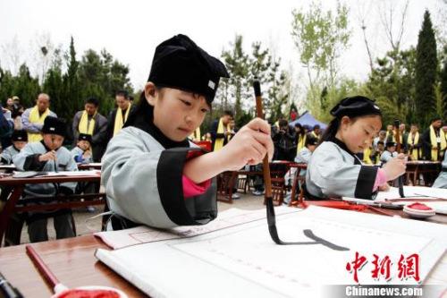 """孔子故里的学童们在夫子洞广场参加戊戌年学童启蒙开笔礼,学写""""人""""字。 沙见龙 摄"""