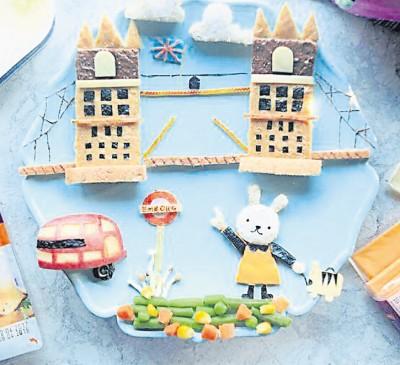 """林美渲将""""伦敦桥""""放入餐盘中,制做材料包括花生酱、面包、芝士条、苹果等,在孩子的餐盘中呈现一道美丽的景色。(马来西亚《星洲日报》)"""