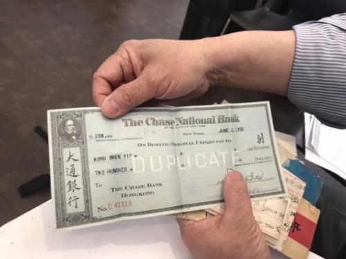 梁晋展示父亲汇款回中国的支票。(记者牟兰/翻拍)