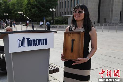 2016年多伦多市政厅前广场举行纪念人头税和排华法案道歉10周年活动。现场展示了当年华工建设加拿大太平洋铁路留下的最后的道钉。(中新社记者 徐长安 摄)