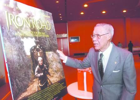 电影《铁路》2009年在加拿大首映,作为铁路华工的后裔及曾缴交过人头税的加拿大铁路华工基金会名誉会长盘占元,看着电影海报大有感触。(图片来源:加拿大《明报》)