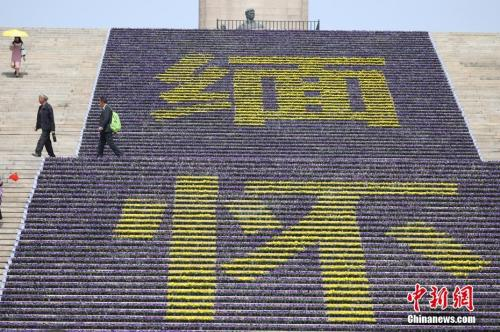 """资料图:3月26日,南京雨花台烈士陵园内的烈士纪念碑前布置了由数万盆鲜花组成的""""缅怀""""花坛,以此表达对革命英烈的纪念之情。 <a target='_blank' href='http://www.chinanews.com/'>中新社</a>记者 泱波 摄"""