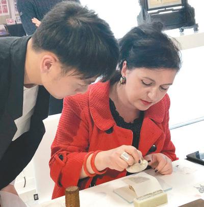 """在伦敦手工艺周""""技艺中国""""展上,一位参观者在体验中国拓印工艺。本报记者 强 薇摄"""
