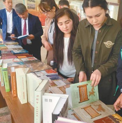 """在""""中国图书进校园""""活动上,阿拉巴耶夫大学师生正在翻阅图书。本报记者 吴 焰摄"""
