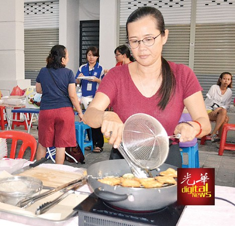 单亲妈妈吕翠云炸五香饼,希望能靠自己的劳力赚取孩子的教育费。(马来西亚《光华日报》)