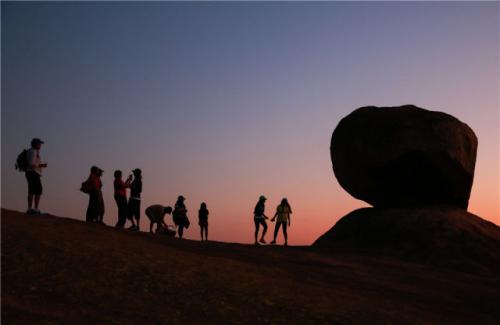 2015年11月9日,在哈拉雷东坡莎瓦山上,几名游客在一处平衡石景点旁边观赏日落。新华社发 王新举摄