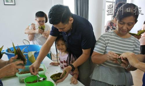 家长带着小朋友一起包粽子,享受假期的亲子乐。(马来西亚《星洲日报》)