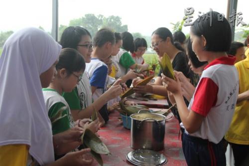 在爱心妈妈的协助下,巫华裔学生都参与裹粽子过程,也得知端午节的来历及典故。(马来西亚《星洲日报》)