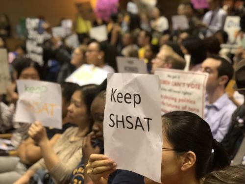 针对特殊高中改革,不少家长带着抗议牌前往参加会议。(美国《世界日报》/黄伊奕摄)