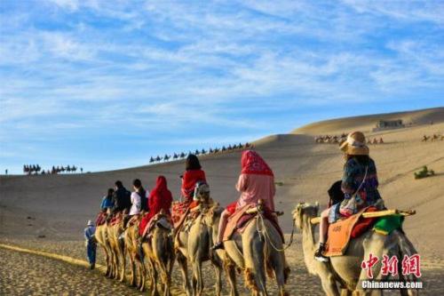 资料图:丝绸之路国际旅游名城甘肃敦煌,鸣沙山月牙泉人流如织、驼队如龙。王斌银 摄