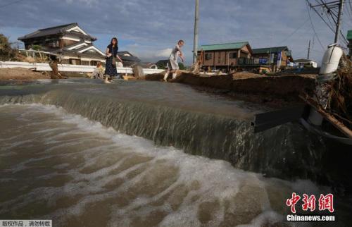 资料图:日本冈山县仓敷市民众走在被水淹没的街道。