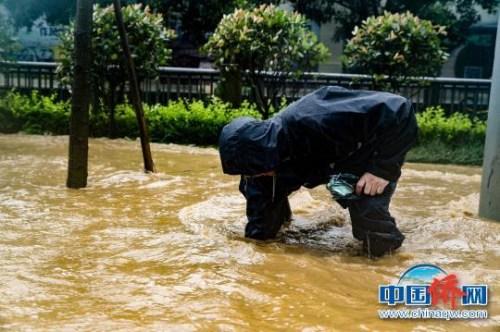 断枝树叶堆积在雨水篦子外导致排水不畅,工作人员徒手清理雨水篦子,确保排水通畅。 成都市城管委 摄