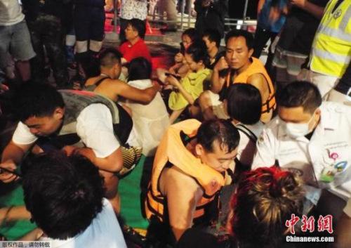 资料图:泰国普吉岛海域附近,一艘观光船发生倾覆。图为救援人员营救被困游客。