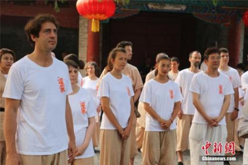 """图为归山朝拜的海外少林弟子,他们的胸前写着汉字""""回家""""。 岳龙 摄"""