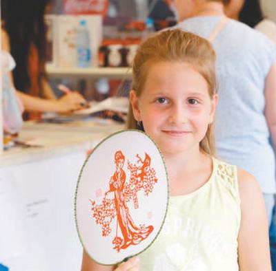 """在""""北京日""""老字号展卖活动中,一位俄罗斯小朋友购买了一把工艺品扇子。   本报记者 王斯雨摄"""