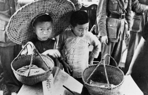 1938年7月7日,武汉民众开展抗日献金运动。这是卖白兰花的儿童把售花所得献给抗日运动。新华社发