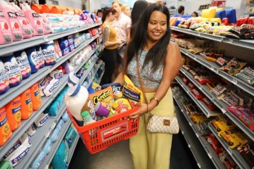 """超市内的一名女客人挑选了一篮子""""食品""""。(美国《侨报》/邱晨 摄)"""