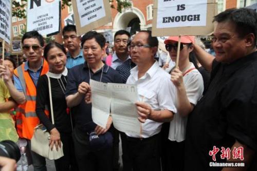 伦敦华埠商会主席邓柱廷(前左3)等侨领在展示致英国内政部的申诉信函。 中新社记者 张平 摄