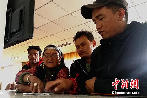 图为今年57岁的尼泊尔商人赞达热·瓦迪(左二)在阿里狮泉河海关普兰工作点的业务大厅内办理通关手续。<a target='_blank' href='http://www.chinanews.com/'>中新社</a>记者 赵延 摄