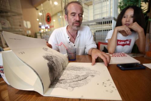 捷克艺术家伊瑞向记者展示其中国画作品集。