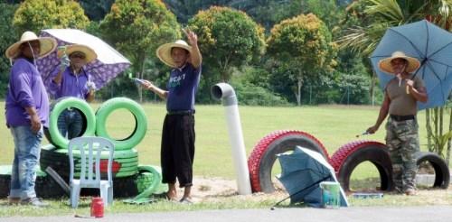 大家戴着草帽、撑着伞,在烈日下美化校园。(马来西亚《星洲日报》)
