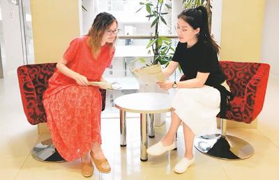 图为工作之余,李妍妍(右)在公司休息区向哈萨克斯坦同事展示介绍中国传统文化的杂志。