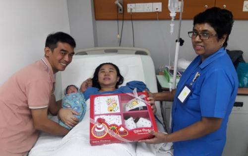 霹雳人民医院的国庆日宝宝与父母,接受霹雳人民医院送上的祝福礼篮。(马来西亚《星洲日报》)