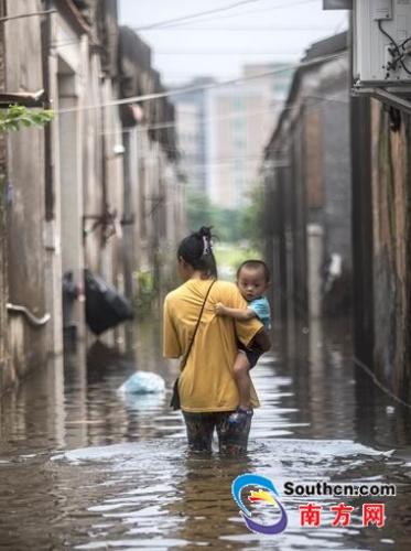 9月2日,陈店镇北沟村,水位开始退去,一名大人带着孩子蹚水回家。南方网全媒体记者 张由琼 实习生 徐杰 摄