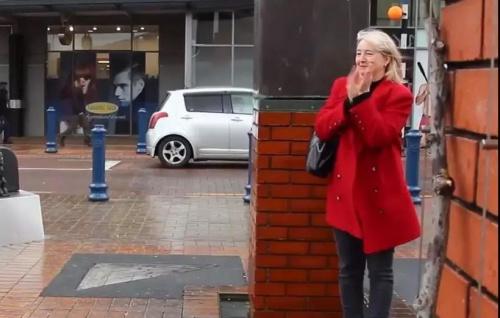 一位冒着风雨观看阿姨们广场舞的新西兰女士。(新西兰天维网)